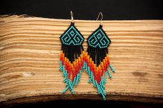 Mexican Huichol inspired geometric design earings.  Black, matte orange, matte deep orange, matte brick red, and matte turquoise beaded earrings with 9.25 sterling silver hooks.  Approximately 4 inches or 10cm long.