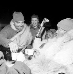Louis Armstrong på Ullevålseter 1959 Styrkedram underveis. For å holde kulden unna serverer Ivar Seter et skyssbeger ved Nordseter til en tilsynelatende noe skeptisk verdensstjerne. Hans Velund i bakgrunnen. Foto: Tore Fredenlund ©