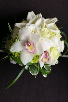 Modern bridal bouquet featuring cymbidium orchids, green tea roses, ivory garden roses, calla lilies, hydrangea, pitt, and lily grass. Photo by; Laren Wakefield Photography http://www.lauren-wakefield.com/#home