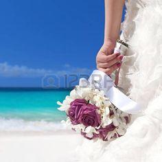 mariage plage: bouquet de mariage dans la main de la mariée sur la plage