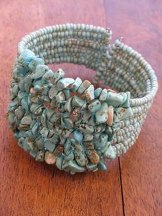 """This Turquoise cuff has nine wired rows of chips and beads .  Open at the back the memory wire makes the bracelet able to fit varying sizes of wrists from 8"""" whilst maintaining its shape."""
