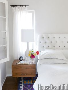 A bouquet of bright roses adds a pop of color to this all-white bedroom in designer Chris Barrett's California bungalow.