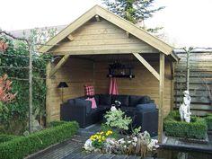 Sfeervol ingerichte overkapping van geïmpregneerd hout. Het dak is voorzien van zwarte dakpannen.