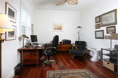 Den with wood flooring and volume ceilings.