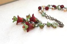 This beautiful necklace is a bouquet of cranberry wine red and fresh green flower blossoms. The cluster of floral charms fall in a gorgeous