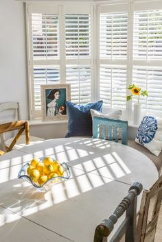 Round white dining table paired with mismatched distressed wooden chairs in a bay window with white shutters.