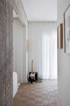 Full height white curtains in Midcentury apartment in Sao Paolo, Brazil by Felipe Hess, Remodelista