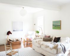 The rocking chair was found on the side of the road and fits the home's aesthetic. Sarah's mom sewed the slipcover for their Pottery Barn sofa. The walls are painted Benjamin Moore Cloud White, giving the space a bright and airy sense. Sarah loves incorporating powdery pastel colors among all of the white walls.