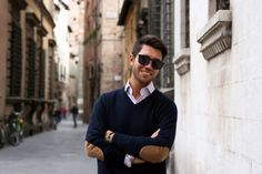 Button-down shirt, navy v-neck sweater with suede elbow patches, watch, bracelet, and sunglasses; fit is everything