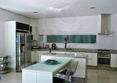 O acesso para a cozinha é feito por meio de uma enorme porta de correr, que pode manter o cômodo integrado às salas ou ser fechado para maior privacidade nos dias de festa, por exemplo.