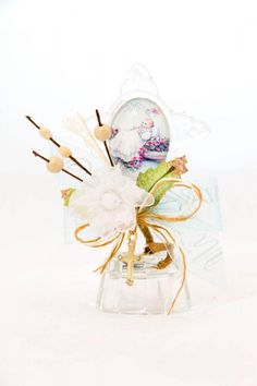 Baptism party favors made out of a glass cross with a picture of a baby being baptized and an artificial flower arrangement all on top of a glass base with a multicolor light.