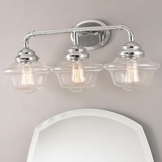 """Timeless Schoolhouse Bath Light - 3 Light Timeless schoolhouse style meets todays design with a contemporary twist on an instant classic. Clear glass and polished chrome add even more timeless appeal. Available in sconce, 2 light bath light and 3 light bath light. (11""""Hx26""""Wx10""""D) 3x60W max per socket, medium base,"""
