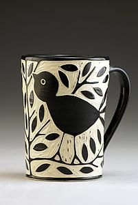 Created by Jennifer Falter Wheel thrown porcelain mug with whimsical blackbirds and branches. The surface of this mug is hand carved through a layer of black slip to create a contrasting and textural surface, using a technique known as sgraffito.
