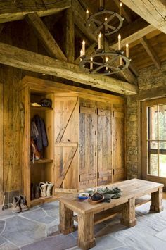 Entryway and mudroom designed with wrought iron, reclaimed wood and stone