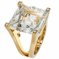 """18kt yellow gold ring featuring a cleaved clear Quartz of 15.7ct that is prong set. There are 8 round brilliant Diamonds with a total weight of .15ct set on top of the prongs and under the """"U"""" basket. This is a Jorge Adeler custom design."""