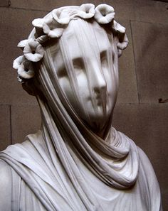 """A """"Veiled Vestal Virgin"""" by Raffaelle Monti (1818-1881). It was commissioned by the sixth Duke of Devonshire on 18 October 1846 and the piece can be dated to 1847. From the time of its arrival from Milan, the statue appears to have been kept at Chiswick House.  It was removed to Compton Place in 1892, and by 1901 it was in the Gallery at Compton Place. In 1999 it was removed to the Sculpture Gallery at Chatsworth where it featured in the recent Pride & Prejudice film."""