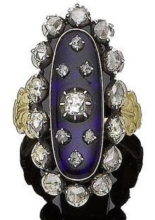 A late 18th century blue glass and diamond ring. The elongated oval blue glass plaque applied with graduated rose-cut diamonds in pinched collet-setting, within a similarly-cut diamond surround, all in closed-back settings, between engraved shoulders of foliate design/