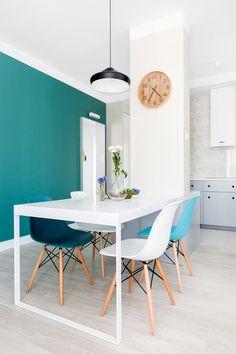 W jadalni krzesła w różnych kolorach ożywiają aranżację, a ciepłą dodają drobne akcenty w odcieniu jasnego drewna.