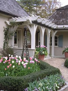 cottage style home with pergola, stone path, shutters and tulips. doesn't get better. :)