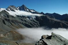 A foggy valley with the glaciated Großglockner in the background