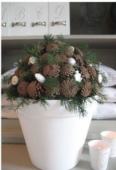 Love this centerpiece with evergreen and pine cones turned bottoms up. Natural Christmas Decorations transition so well to Winter.