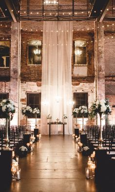 We're feeling the ambiance in this elegant wedding alit with a romantic glow thanks to candle aisle markers, string lighting, and chandeliers, coupled with rugged brick walls and a gauzy fabric for a warm and inviting vibe. Romantic Wedding Receptions, Romantic Weddings, Wedding Ceremony, Wedding Venues, Wedding Ideas, Decor Wedding, Wedding Styles, Wedding Aisle Candles, Wedding Favors