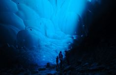 Glacial Cave: Hikers under the Mendenhall Glacier near Juneau, Alaska. When conditions are right, streams melt holes into the glacier. At times they are large and stable enough for exploration. The ice filters out most colors of light except for the blue wavelengths leaving a stunning blue glowing from the ice above. (© Mark Meyer/National Geographic Photo Contest)