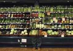 "Artist Liu Bolin demonstrates an art installation by blending in with vegetables displayed on the shelves at a supermarket in Beijing November 10, 2011. Liu, also known as the 'Vanishing Artist', started practising being ""invisible"" by means of optical illusions more than six years ago. Picture taken November 10, 2011. (REUTERS/China Daily)"