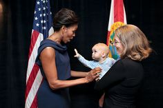 "A child reaches out to First Lady Michelle Obama prior to a Faith and Community Groups Leading the Way event at Northland, A Church Distributed, in Longwood, Fla., Feb. 11, 2012. The event was held in celebration of the second anniversary of the ""Let's Move!"" initiative.(Official White House Photo by Chuck Kennedy)"