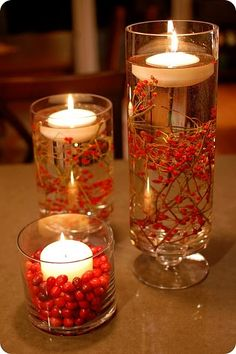 As is probably clear right now, I like submerged items in clear cylindrical vases with floating candles on top. I think the red berries are too Christmasy, but I like the setup.