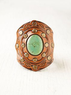 Beautiful leather cuff with turquoise stone and stud detailing. Snap button closure.