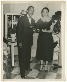Mae Reeves and her husband Joel pose with her hats at Mae's Millinery in Philadelphia, circa 1953. In 1942, a time when few women were becoming entrepreneurs, Reeves opened what would become a Philadelphia institution with a $500 bank loan. Her hat shop, Mae's Millinery, helped dress some of the most famous African-American women. (Collection of the Smithsonian National Museum of African American History and Culture, Gift from Mae Reeves and her children, Donna Limerick and William Mincey…