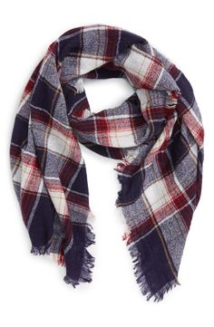 Classic plaid details this airy scarf woven from soft wool and trimmed with dainty fringe.