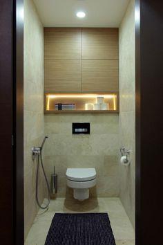 petite salle de bains avec un carrelage aspect pierre, niche lumineuse et armoires murales en bois