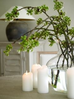simple yet effective- a few white candles and a branch in a glass vase, that's all it takes...