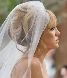 Not super crazy about the updo design, but it shows what a veil and bangs can look like.
