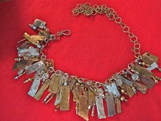"Spare parts necklace:  sterling silver, brass, copper, bronze, etc, stamped in Hebrew ""Make a Joyful Noise,"" and it does."