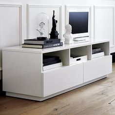 CB2 Chill White Media Console - two or three lined under living room windows with TV on top. In drawers, games, blankets, DVDs, magazines, purses(?).