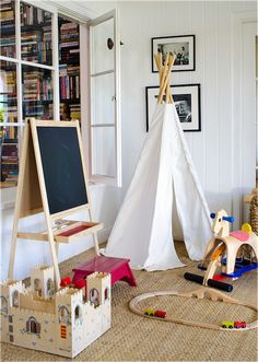 Adorable playroom with white tongue and groove paneled walls accented with black and white framed photography over a white teppee