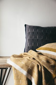Modern and oh so soft, this navy blue cushion in the Origin collection is patterned with a linear design and woven from super soft Merino wool in the UK.
