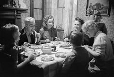 Ministry of Information Photo Division Photographer -- Jane Meredith and Phyllis Morris of the Old Vic Travelling Theatre Company, enjoy a meal with Mr and Mrs Bailey, a miner and his wife, at their home in Trealaw, Wales during 1941. The children are Margaret and Douglas Ashington, evacuees from Birmingham.