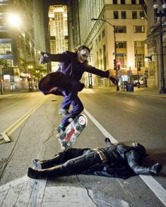 Heath Leger Skate boarding over Batman while they take a break on the set of The Dark Knight.