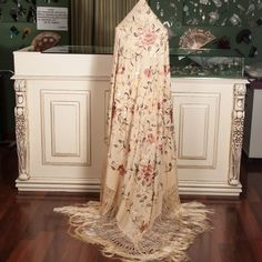 Mantón  de manila confeccionado  a mano en tela e hilo de seda natural.Bordado y flecado totalmente a mano.En su bordado podemos apreciar entre otras flores el clavel ,siendo junto a la rosa una de las flores mas conocidas y demandada en todo el mundo.