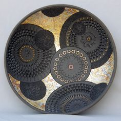 Julie Berndt: Highly textured wall pieces and vessels with additions of inset stones, woven reed, and gold leaf. Each stone is collected by me, and the image of it is carved into the clay, which is then fired, and the stone is set. Each impression, scoop, or piercing is made one at a time, forming the contrasting shapes.