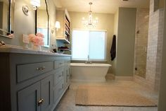 """Benjamin Moore """"Fieldstone"""" cabinets with white marble counter top, Allen + Roth Frameless Arch mirrors, honed carrara marble hex tiles on the floor, green grey walls, West Elm Pebble Rug, subway tiles surround shower"""