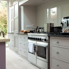 This classic kitchen has smart painted cabinetry. A duel-fuel range cooker has been teamed with a custom-made extractor and glass splashback for a streamlined look. Like the stainless steel look handles.