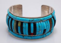 This handcrafted Zuni cuff is stunning! Made of Sterling Silver and inlaid with rows of turquoise, coral, jet, jade and agate. In excellent condition with no cracks or missing stones. Unfortunately, the previous owner did scratch their name, Sally, on the inside in two places. It is not very deep however and could most likely be rubbed out without removing much of the surface. Inside is stamped Sterling and signed by the artist J.M. (cuff) & Jesver (stone inlay). Cuff width is 1.25. Inside…