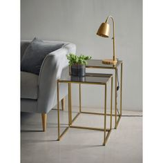 Inspired by contemporary Scandinavian design, our set of two square nesting tables will make a fabulous addition to any living space. This set consists of one smaller and one larger table, each piece featuring a black glass top and slender, an