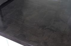 Use ARDEX to coat existing countertops with concrete. Then use CONCRETE STAIN to color them and seal with WT-LOOK Sealer.