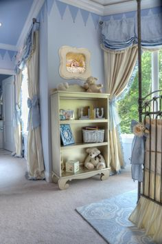 An antique silver shelf displays sweet baby accessories in this light blue nursery. A painted blue pennant lines the crown molding, adding a playful touch to the elegant space.